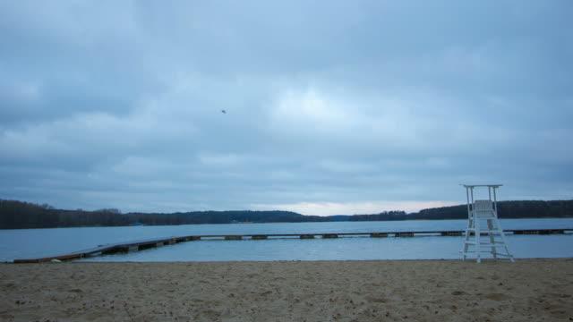 piovosa giornata presso la spiaggia di sabbia bianca con bagnino stand-gabbiani - cabina del guardaspiaggia video stock e b–roll