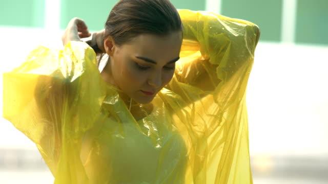 vídeos de stock, filmes e b-roll de dia chuvoso: mulher de capa de chuva amarela - capa de chuva