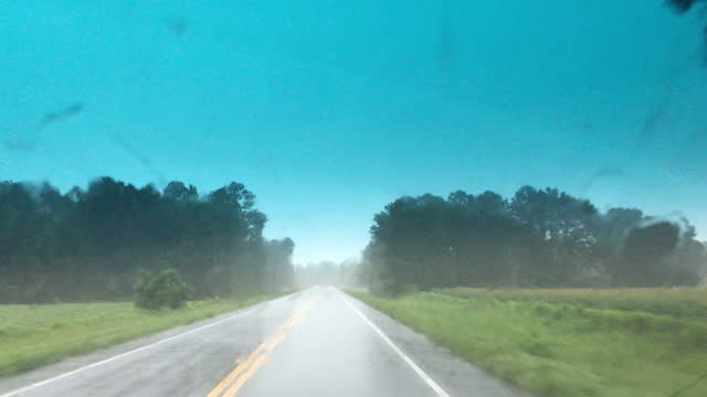 rainy drive down never- ending curve on rural road with agricultural fields - general motors stock videos & royalty-free footage