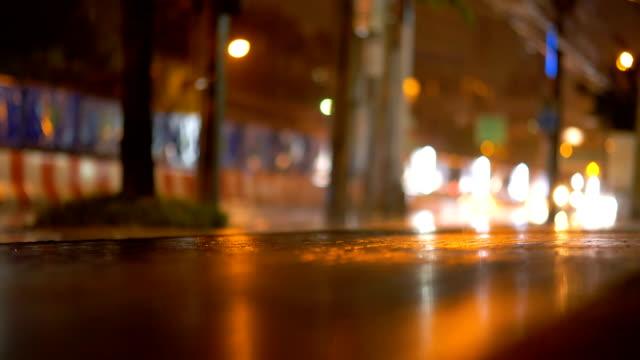 vidéos et rushes de pluie du soir, notion de météo, trafic, rues urbaines, asphalte, éclairée par les réverbères. mode de vie de la ville moderne. - trottoir