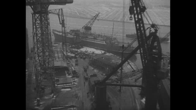 vs rainy foggy shipbuilding yard in clydebank scotland with ships in various stages of construction // car chassis is lowered onto assembly line in... - skeppsbyggare bildbanksvideor och videomaterial från bakom kulisserna