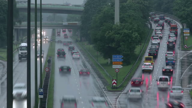 stockvideo's en b-roll-footage met t/l rainy highway with traffic-packed off ramp / munich, bavaria, germany - versmelten