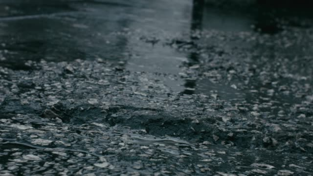vídeos de stock e filmes b-roll de rainy weather with physical sound of rain and an asphalt road with pebbles,  gravel, water ponds and raindrops - alfalto