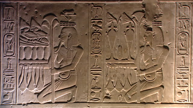 raised relief of kneeling nome-gods. david-rohl passes in silhouette from left to right. unpainted relief from the hypostyle hall , temple of abydos. - symbol stock videos & royalty-free footage