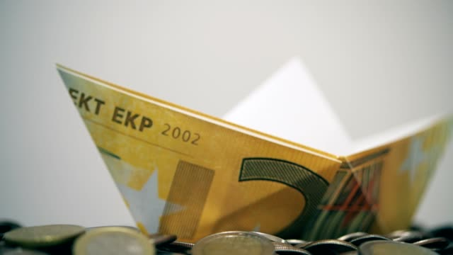 raising euro paper boat over euro coins - capsizing stock videos and b-roll footage