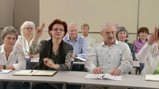 stockvideo's en b-roll-footage met hd: raising hands for voting on the seminar - menselijke arm