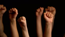 Raising hands with fists on black background