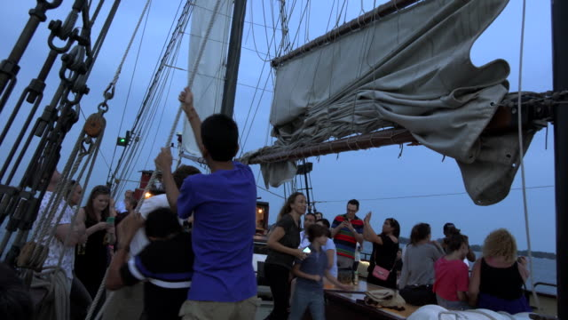 raising the sail in tourist cruise in lake ontario / sightseeing cruises give tourists an amazing view of the urban toronto skyline so they are a... - hoisting stock videos & royalty-free footage