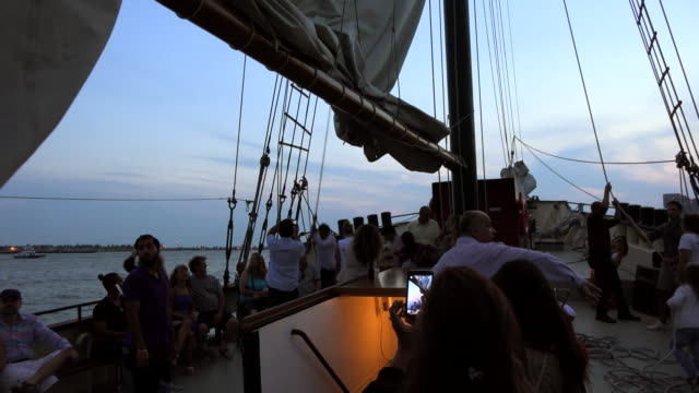 raising the sail on tourist cruise on lake ontario / sightseeing cruises give tourists an amazing view of the urban toronto skyline, so they are a... - ontariosee stock-videos und b-roll-filmmaterial