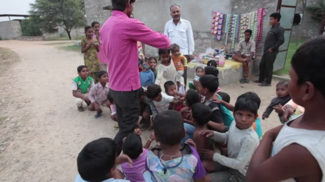 rajasthan india october 30 2014 a school teacher in a small village in rajasthan gives sweets to small school girls and boys children from lower... - grundschüler stock-videos und b-roll-filmmaterial
