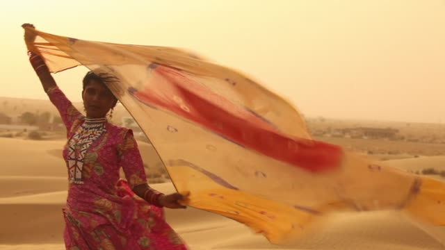 vídeos y material grabado en eventos de stock de rajasthani woman blowing her dupatta on desert, sam desert, jaisalmer, rajasthan, india - india