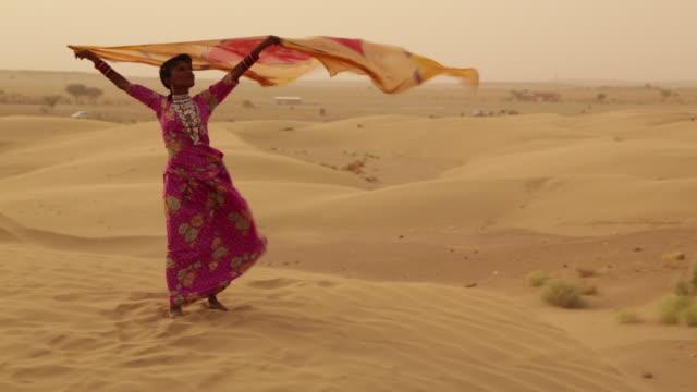rajasthani woman blowing her dupatta on desert, sam desert, jaisalmer, rajasthan, india - 知覚点の映像素材/bロール