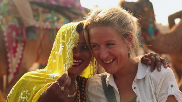 rajasthani woman enjoying with a adult woman in the fair, pushkar, rajasthan, india - tourist stock-videos und b-roll-filmmaterial