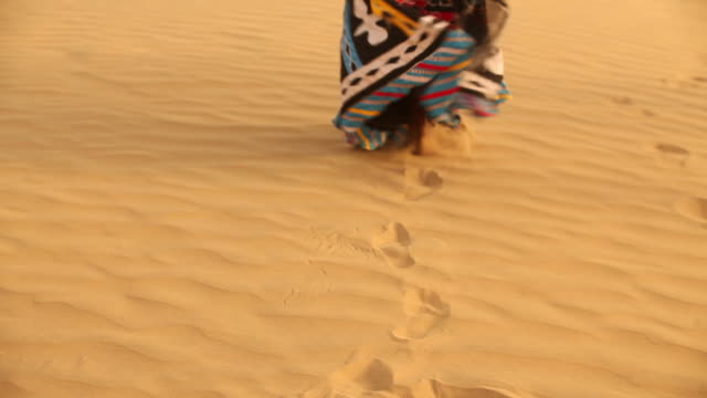 rajasthani woman walking on desert, sam desert, jaisalmer, rajasthan, india - fußabdruck stock-videos und b-roll-filmmaterial