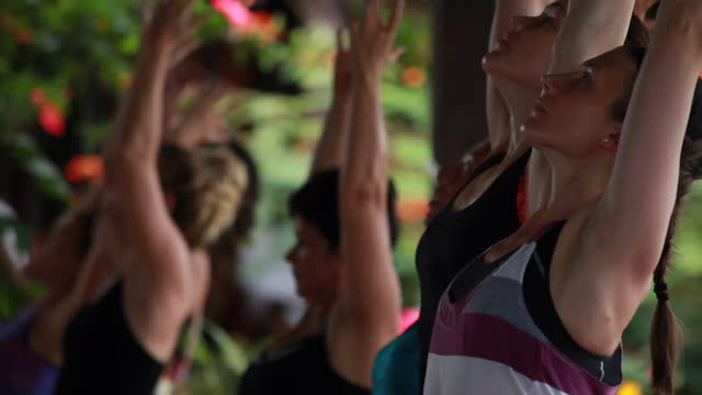 raking shot close-ups of women in colourful yoga attire practising yoga postures on an outdoor yoga deck surrounded by colourful vegetation and then a yoga teacher corrects a posture of a woman practising yoga - kelly mason videos stock videos & royalty-free footage