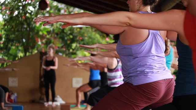 raking shot of a group of women practising yoga with close-ups on their hair, hands and arms on an outdoor yoga deck surrounded by lush vegetation - kelly mason videos stock videos & royalty-free footage