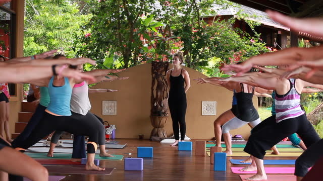 a raking shot of women and a solo man on an outdoor yoga deck bend over as we shoot over their heads we see the yoga teacher in the background and all of the yoga students stand up to open up the shot. - kelly mason videos stock videos & royalty-free footage