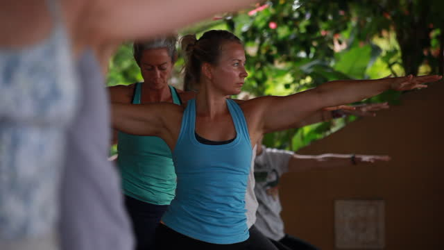 a raking shot of women practising yoga and then focussed on a woman moving into warrior pose surrounded by women and colourful yoga mats - kelly mason videos stock videos & royalty-free footage