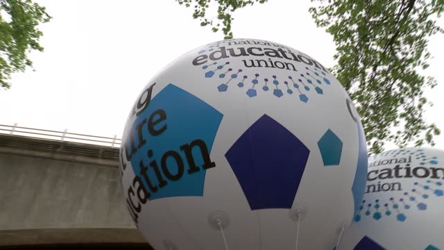 GVs and interviews ENGLAND London Embankment EXT Various of people with balloons and placards ahead of march / protesters wearing Theresa May masks /...