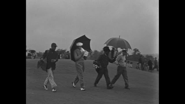 Ralph Guldahl gallery with several umbrellas at the Augusta National Invitational / Guldahl drives / men caddies umbrellas / Ben Nelson hits drive...