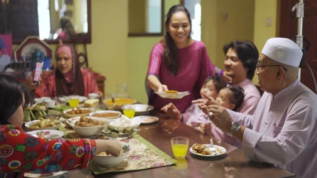 ラマダンハリラヤ孫娘は偉大な祖父に甘い食べ物を提供し、マレーシアのイスラム教徒の多世代の家族はダイニングルームで自宅で夕食を楽しんでいます - 巡礼点の映像素材/bロール