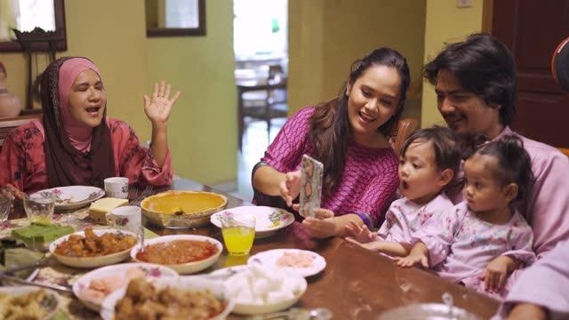 ramadan hari raya malaysian muslim multi generation family waving videocall relative enjoying dinner at home in dining room - malaysian culture stock videos & royalty-free footage