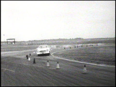 ws rambler american custom coming out of a turn on inner track at the daytona international speedway ws same shot but a chevrolet corvair makes the... - circuito di daytona video stock e b–roll