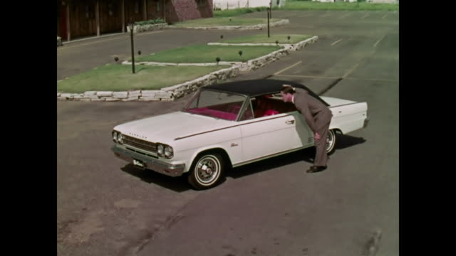 1966 amc rambler rebel hardtop driving through the suburbs - sun visor stock videos and b-roll footage