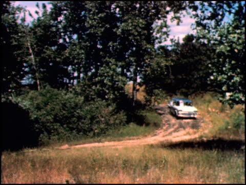 ws rambler six sedan drives along on a country dirt road / xws rambler driving along a winding road / ws two hunters get out of the rambler and grab... - sedan stock videos & royalty-free footage