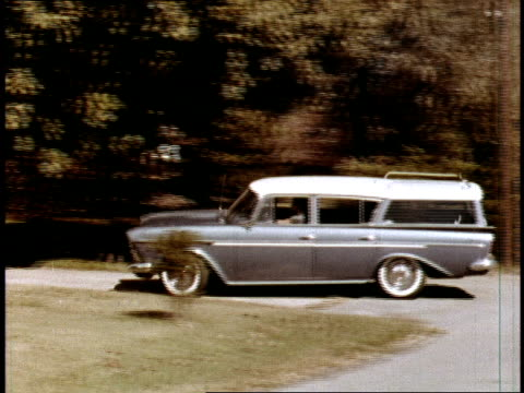 rambler station wagon pulls into the driveway of a typical kennedyera suburban american home / ws young mother gets out of the car and lifts her... - american culture stock videos & royalty-free footage