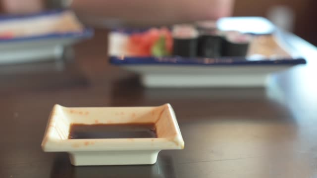 ramekin of soy sauce in front of sushi plate - wasabi stock videos and b-roll footage