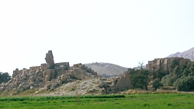 ramesseum. pan-right across the ruins of the ramasseum to gurneh village. - tempio di hatshepsut video stock e b–roll