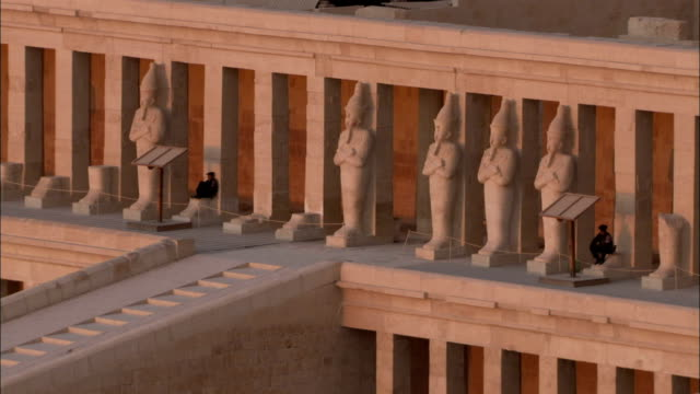 a ramp leads to the temple of hatshepsut entrance lined with pillars and statues. available in hd. - hatschepsut tempel stock-videos und b-roll-filmmaterial