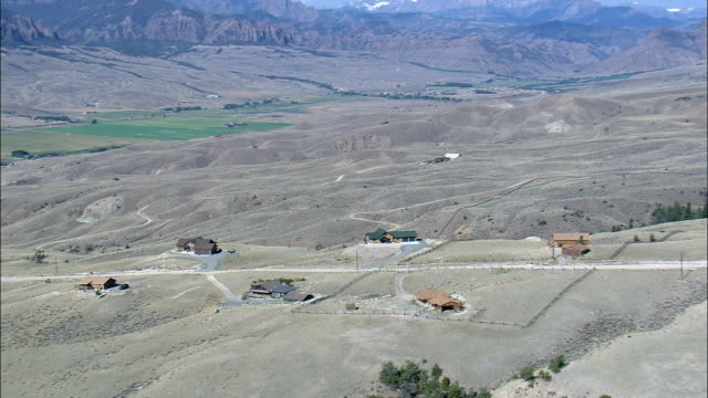 ranch style houses in shadow of mountains  - aerial view - wyoming,  park county,  helicopter filming,  aerial video,  cineflex,  establishing shot,  united states - wyoming ranch stock videos & royalty-free footage