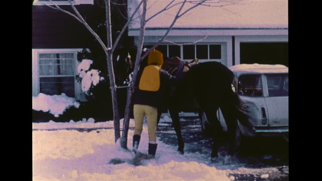 ranch style suburb home, vs teenage females in coats leading horses out of garage barn into snow covered yard, saddling, placing bridle on taller... - bridle stock videos & royalty-free footage