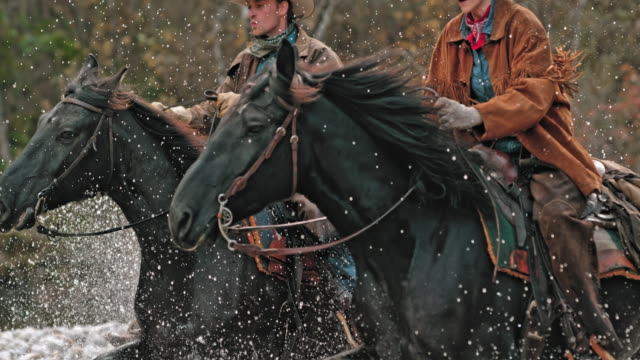 SLO MO TD Ranchers on galloping horses crossing river