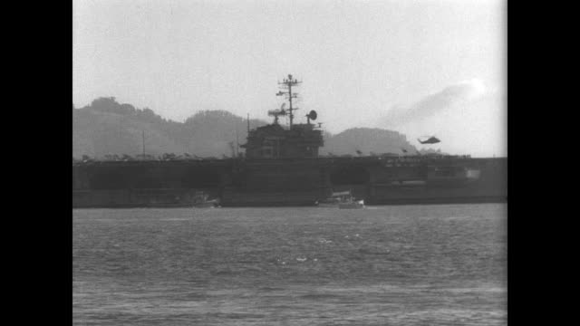 uss ranger ship arrives in san francisco / pan of ship's side as helicopters fly overhead / crowd with welcome home banner stand on the shore /... - 1966 stock videos & royalty-free footage