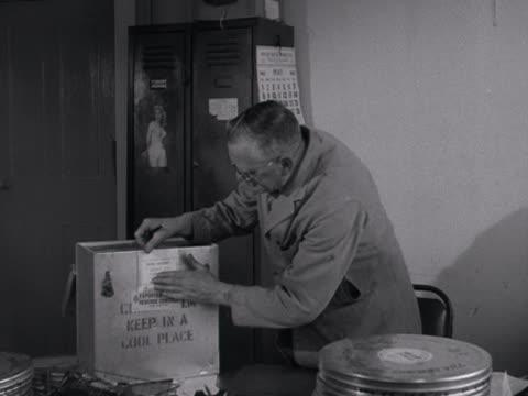 vidéos et rushes de rank distribution storeman boxes up film cans to be delivered to various cinemas across the united kingdom. - boîte de film