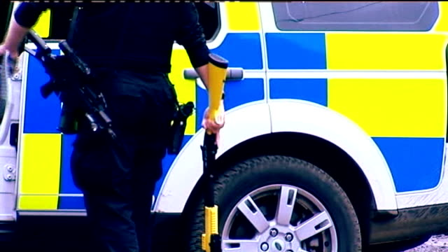 raoul moat inquest findings r09071008 nr morpeth cragside house ext police firearms officer carrying x12 taser gun as along to vehicle - moat stock videos & royalty-free footage
