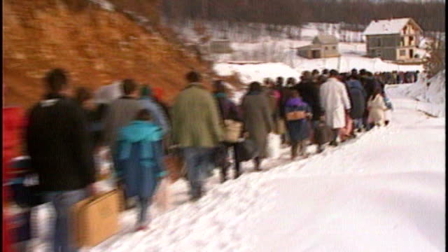 Hague to deploy experts to Syria / Jolie campaign TX Long line of refugees walking away along snow covered road Soldiers around house Legs of...