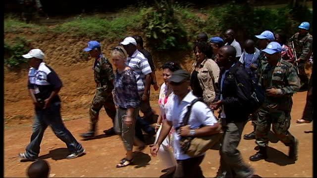 rape victims; kampala: ext wallstrom and party, along with un peacekeepers, walking into village women waving from outside their huts - offer människoroller bildbanksvideor och videomaterial från bakom kulisserna