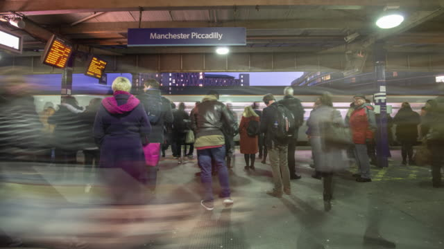 a rapid buildup of commuters gather on the station platform waiting for trains to arrive during the evening rush hour at manchester piccadilly station - railway station platform stock videos & royalty-free footage