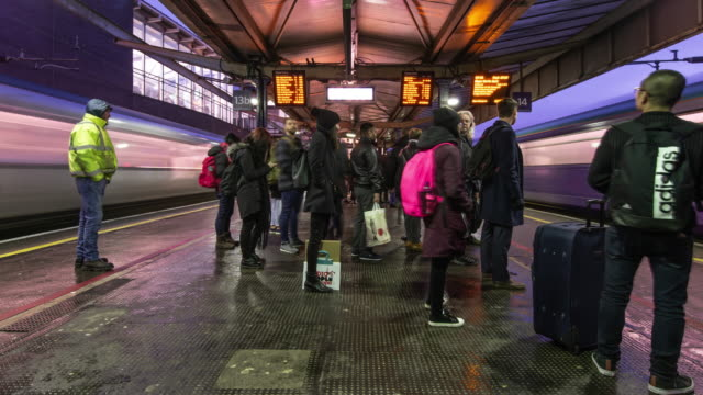 a rapid buildup of commuters gather on the station platform waiting for trains to arrive during the morning rush hour at manchester piccadilly station - clock stock videos & royalty-free footage