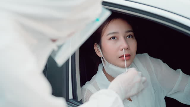 車の中で急速なコロナウイルスのテスト。 - 人間の鼻点の映像素材/bロール