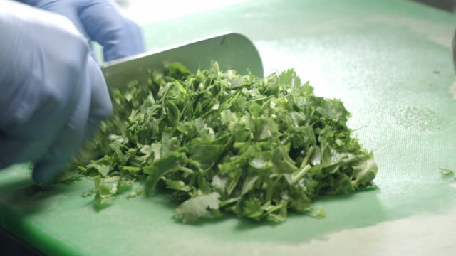 cu rapid cutting of parsley on cutting board in deli section of supermarket - parsley stock videos and b-roll footage