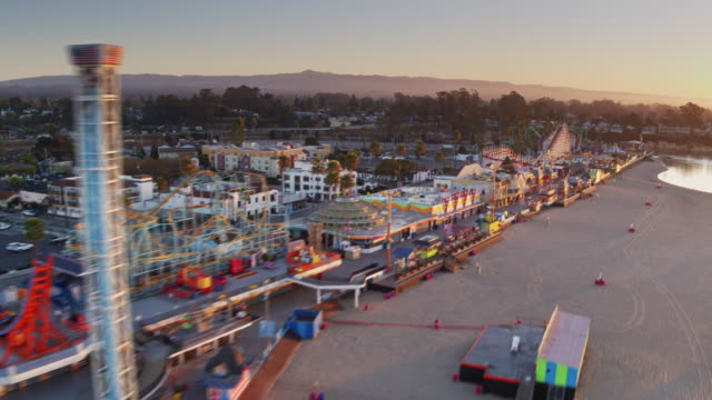 rapid drone flight over santa cruz beach and boardwalk at dawn - santa cruz california stock videos and b-roll footage