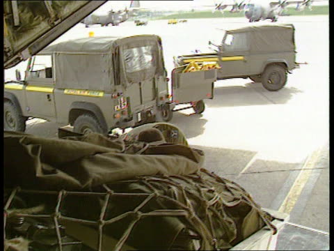 Hostages ENGLAND Wiltshire RAF Lyneham UN landrover along PAN LR PULL OUT as past line of Hercules transport planes MS Soldier in fatigues directing...