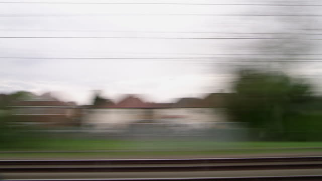 A rapidly moving view from an train window running parallel to the tracks travelling towards London