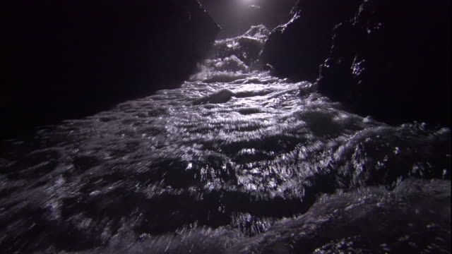 Rapids tumble over rocks inside a cave. Available in HD.
