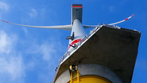 rare low angle view on professional rope access technician - industrial climber (manual high worker) climbing on gigantic offshore wind-turbine on ladder and wind turbine turning above him, blue sky with cloud and sunny. - turbine stock videos & royalty-free footage